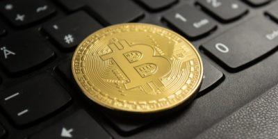 Closeup shot of a bitcoin put on a black computer keyboard